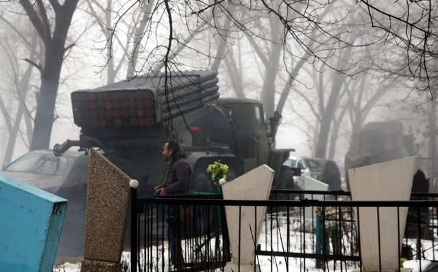 A pro-Russian separatists Grad multiple rocket system launcher is parked in front of a cemetary in the eastern Ukrainian city of Donetsk on January 20, 2015. The past week's escalation in fighting and effective shredding of a repeatedly violated September truce has been accompanied by claims from Kiev's pro-Western government that 700 new Russian soldiers. (Photo by Alexander Gayuk/AFP Photo)