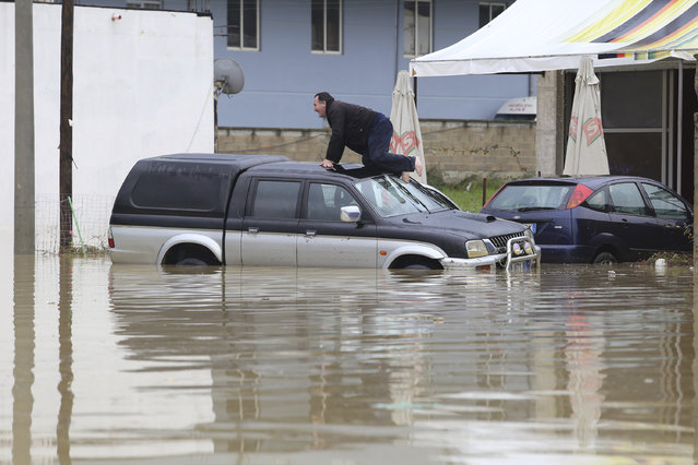 A man crawls onto the roof of a flooded car in Kashar, 10 kilometers (6 miles) from the capital Tirana. Tuesday November 8, 2016. Albanian authorities have sent army troops and other personnel to help people evacuated because of floods caused by heavy rain. No injuries or deaths have been reported so far. (Photo by Hektor Pustina/AP Photo)