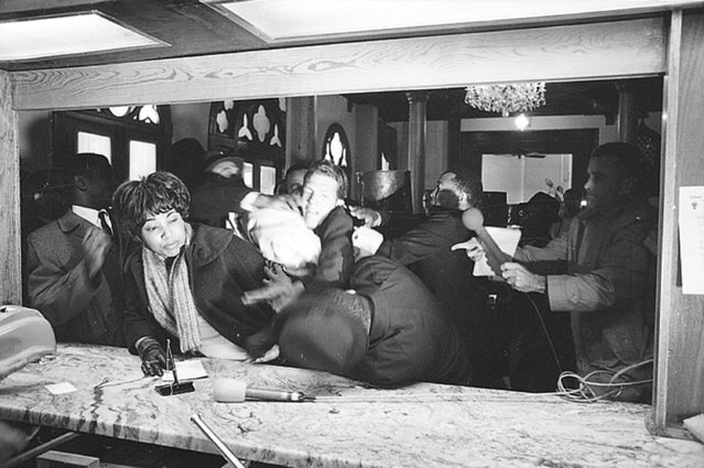 Civil rights leader Dr. Martin Luther King Jr. is attacked by States Rights Party member Jimmy Robinson as King tries to register at the Hotel Albert in Selma, Ala., January 18, 1965. The woman at left is trying to avoid the altercation. King was not injured. (Photo by Horace Cort/AP Photo)