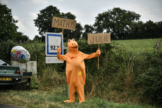 "A spectator dressed in a fancy costume of Casimir, a character of the 1970s – 1980s French television show ""L'Ile aux Enfants"", waves from the side of the route during the seventh stage of the 105th edition of the Tour de France cycling race between Fougeres and Chartres, western France, on July 13, 2018. (Photo by Marco Bertorello/AFP Photo)"