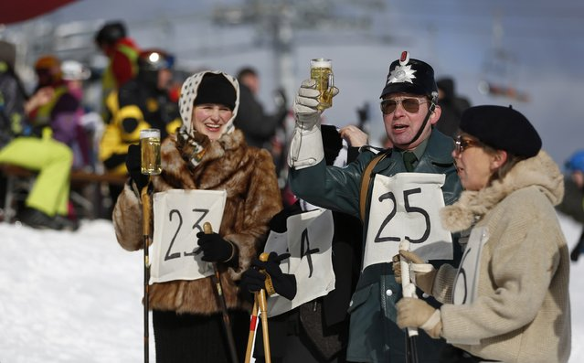 """Participants drink a beer after competing in the """"Nostalgic Ski Race"""" in the western town of Neuastenberg February 8, 2015. (Photo by Ina Fassbender/Reuters)"""