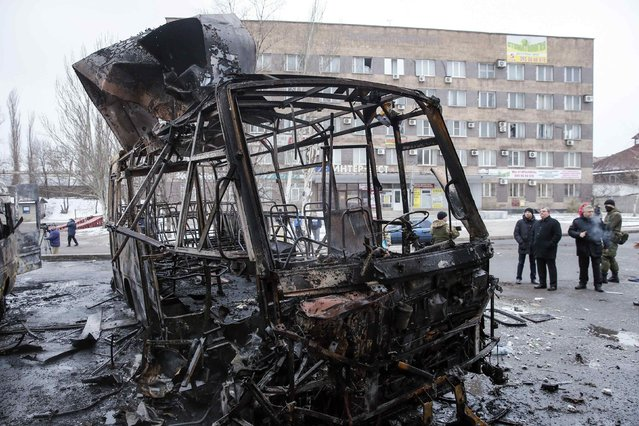 People gather near a destroyed vehicle at a bus station after shelling in Donetsk, February 11, 2015. (Photo by Maxim Shemetov/Reuters)
