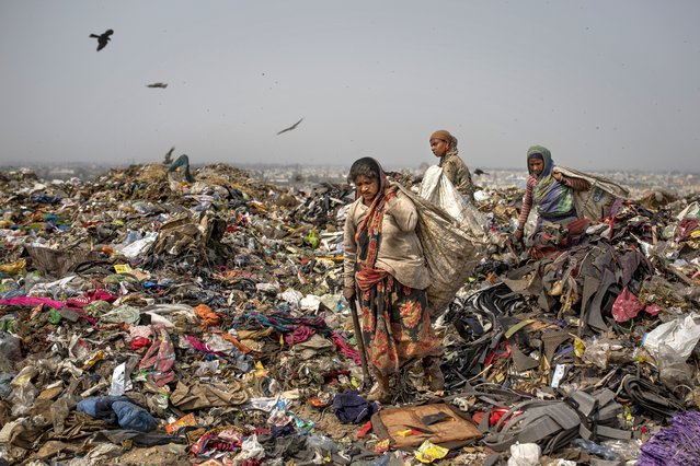 Trash pickers look for recyclable waste at the Bhalswa landfill on the outskirts of New Delhi, India, Wednesday, March 10, 2021. An estimated 20 million people around the world help keep cities clean by scavenging through landfills and dumps. Experts say these trash pickers, who sometimes toil alongside paid municipal sanitation workers, provide a vital service, yet they usually are not on a priority list for coronavirus vaccines. (Photo by Altaf Qadri/AP Photo)