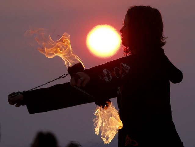 Krissy Humphreys performs with fire at sunrise at the Temple of Whollyness. (Photo by Jim Urquhart/Reuters)