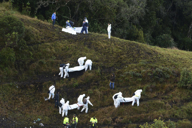 Rescue workers carry the bodies of victims of an airplane that crashed in a mountainous area outside Medellin, Colombia, Tuesday, November 29, 2016. The plane was carrying the Brazilian first division soccer club Chapecoense team that was on it's way for a Copa Sudamericana final match against Colombia's Atletico Nacional. (Photo by Luis Benavides/AP Photo)