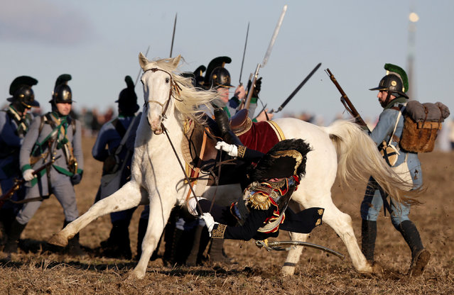A history enthusiast, dressed as a soldier, falls from his horse during the re-enactment of Napoleon's famous battle of Austerlitz near the southern Moravian town of Slavkov u Brna, Czech Republic December 3, 2016. (Photo by David W. Cerny/Reuters)