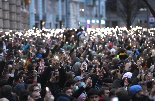 Opposition supporters hold their cell phones during a rally in support of jailed Kremlin critic Alexei Navalny, in central Moscow on April 21, 2021. Jailed Kremlin critic Alexei Navalny's team called for demonstrations in more than 100 cities, after the opposition figure's doctors said his health was failing following three weeks on hunger strike. (Photo by Kirill Kudryavtsev/AFP Photo)