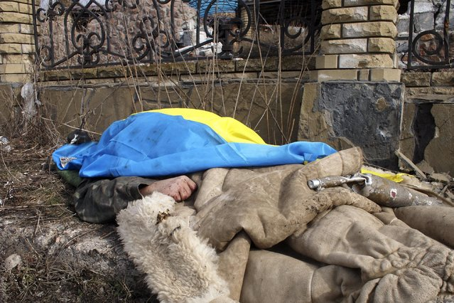 A body of a government soldier lies by the side of the road and is covered by a Ukrainian national flag in the east Ukraine town of Debaltseve on Thursday, February 19, 2015. (Photo by Peter Leonard/AP Photo)