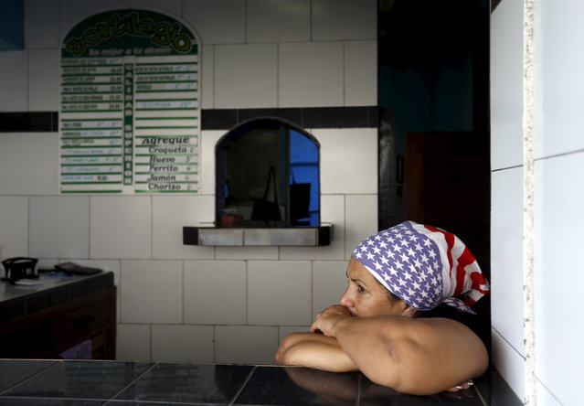 A Cuban woman waits for costumers in her private cafeteria, while wearing a scarf with the colors of the U.S. flag, in Havana April 11, 2015. (Photo by Reuters/Stringer)