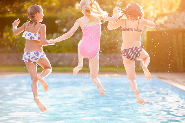 Group of girls playing in outdoor swimming pool. (Photo by Alamy Stock Photo)