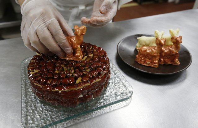 A chef places a goat-shaped chocolate, which is painted with edible gold powder, on a cake celebrating the upcoming Chinese Lunar New Year, during a photo opportunity at a kitchen of Kerry Hotel in Beijing, February 12, 2015. (Photo by Kim Kyung-Hoon/Reuters)