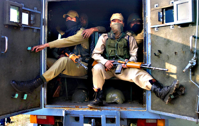 Indian paramilitary soldiers sit inside an armored vehicle near the site of a gun-battle in the outskirts of Srinagar, India, Thursday, October 3, 2013. Police said that at least seven policemen were wounded in an overnight gun-battle with suspected militants in the city of Srinagar. Police further said that militants managed to escape from the security cordon in the city. (Photo by Dar Yasin/AP Photo)