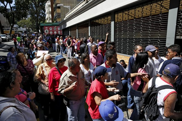 People line up to try to buy corn flour and rice, outside a supermarket in Caracas January 16, 2016. (Photo by Carlos Garcia Rawlins/Reuters)