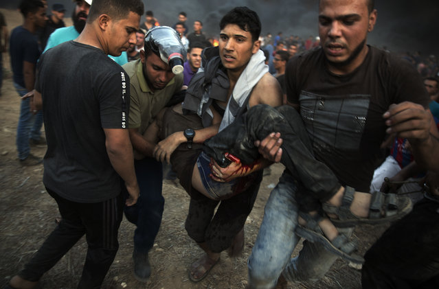 Palestinian protesters evacuate a wounded man shot by Israeli troops during a protest at the Gaza Strip's border with Israel, Friday, October 12, 2018. (Photo by Khalil Hamra/AP Photo)
