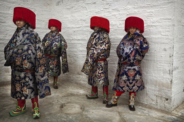 Tibetan Buddhists wear traditional clothing as they wait to take part in a procession during Monlam or the Great Prayer rituals on March 4, 2015 at the Labrang Monastery, Xiahe County, Amdo, Tibetan Autonomous Prefecture, Gansu Province, China. (Photo by Kevin Frayer/Getty Images)