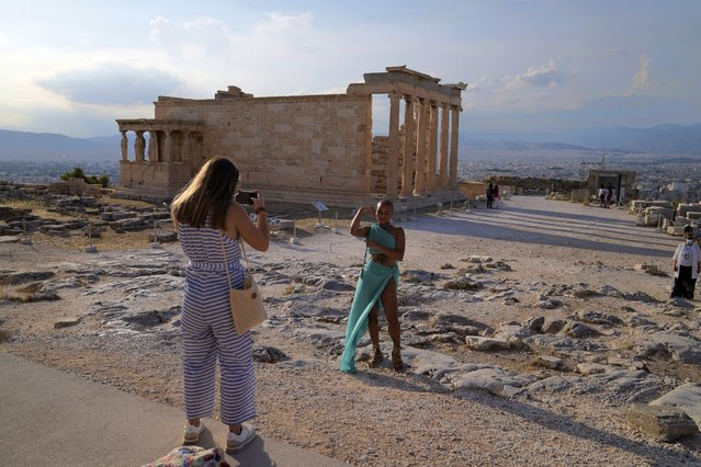 In this Tuesday, June 8, 2021 file photo, a tourist take photos at the Parthenon temple during a media tour for the Foreign Correspondents organised by the Greek Cultural Ministry at the Acropolis hill in Athens. Europe is opening up to Americans and other visitors after more than a year of COVID-induced restrictions. European governments hope to lure back tourists – and their dollars – back to the continent's trattorias, vistas and cultural treasures. (Photo by Thanassis Stavrakis/AP Photo/File)