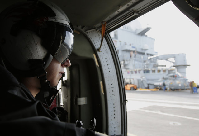 A U.S. military officer looks out at the flight deck of the French navy aircraft carrier Charles de Gaulle in the Persian Gulf as the U.S. helicopter prepares for takeoff Thursday, March 19, 2015. (Photo by Hasan Jamali/AP Photo)
