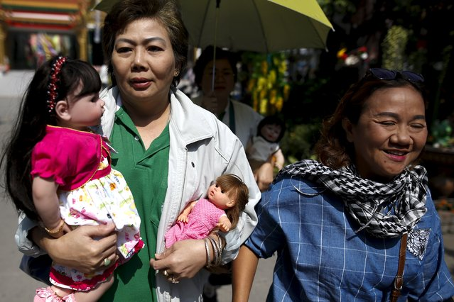 "Women carry ""child angel"" dolls to a Buddhist monk to be blessed at Wat Bua Khwan temple in Nonthaburi, Thailand, January 26, 2016. (Photo by Athit Perawongmetha/Reuters)"