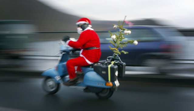 A man disguised as Santa Claus rides on a scooter to an annual biker's meeting, on December 24, 2016 in Hagen, western Germany. (Photo by Ina Fassbender/AFP Photo/DPA)