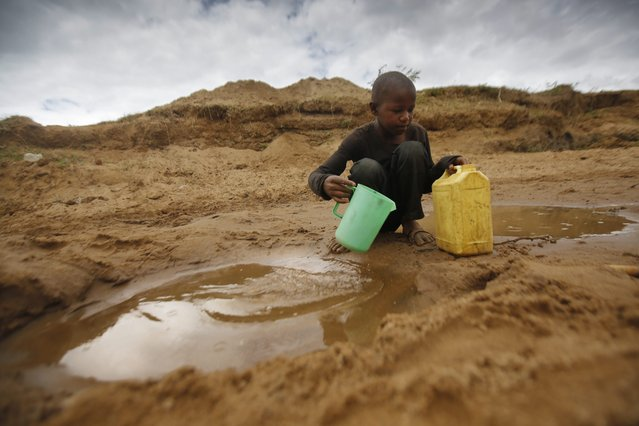 A young boy scoops water from a hand-dug well in the dry riverbed near Matinyani, in the semi-arid Kitui County in southeastern Kenya, 22 March 2015, the World Water Day. Residents of Kitui County and other arid and semi-arid areas of the country have been hard-hit by extremely poor rainfall this year while the government said in previous month that some 1.6 million people countrywide are facing acute starvation due to the drought and will need relief food over the next six months. (Photo by Dai Kurokawa/EPA)