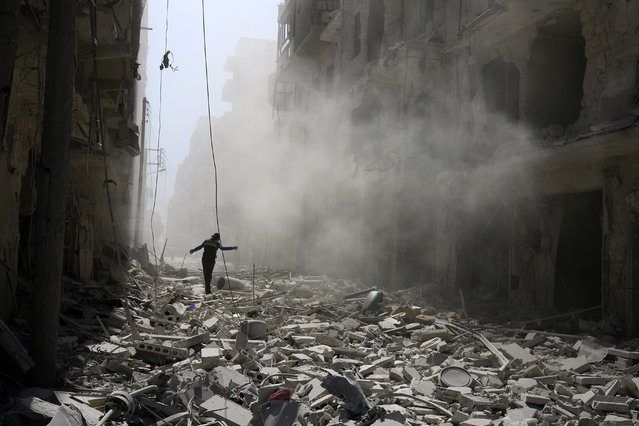 SYRIA: A man walks on the rubble of damaged buildings after an airstrike on the rebel held al-Qaterji neighbourhood of Aleppo, Syria September 25, 2016. (Photo by Abdalrhman Ismail/Reuters)