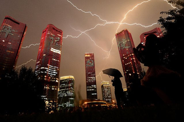 People look at buildings displaying a light show on the eve of the 100th anniversary of the Chinese Communist Party in Beijing on June 30, 2021. (Photo by Noel Celis/AFP Photo)