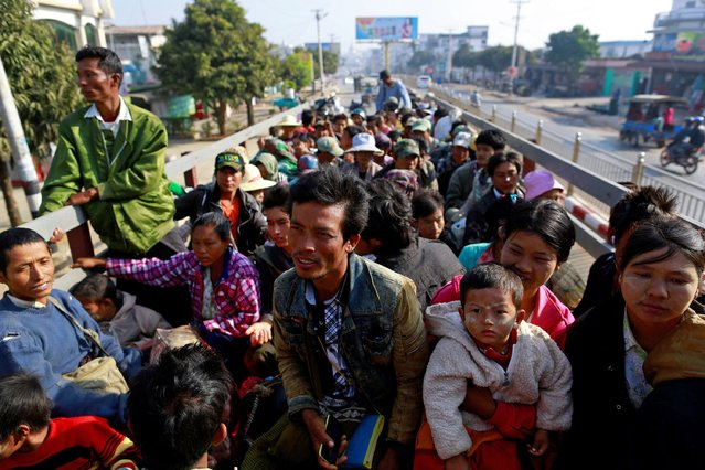 Migrant workers who fled from Karmine ride a vehicle to return home, after staying at a temporary refugee camp in Lashio February 21, 2015. (Photo by Soe Zeya Tun/Reuters)