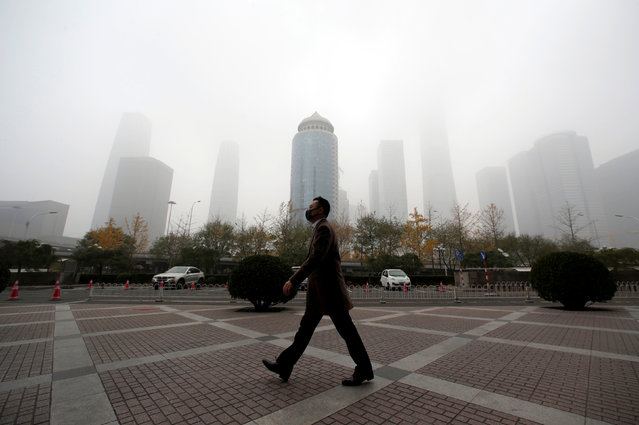 A man wearing a mask walks in the central business district on a polluted day after a yellow alert was issued for smog, in Beijing, China November 14, 2018. (Photo by Jason Lee/Reuters)