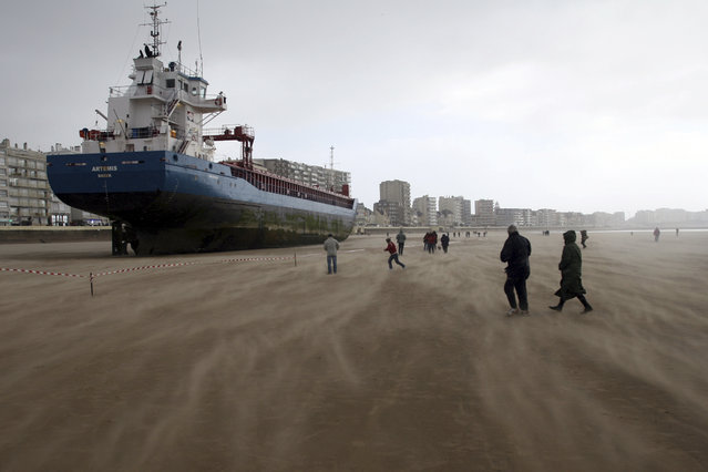 Locals and tourists walk around the Dutch ship Artemis which ran aground on the beach of les Sables d'Olonne, southern French Britanny, western France, March 10, 2008. The ship was driven onto the coast by high wind. (Photo by Stephane Mahe/Reuters)