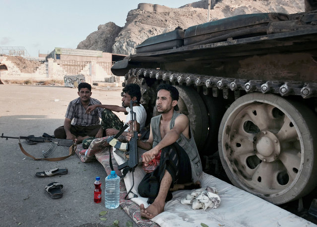 In this photo taken Saturday, March 21, 2015, members of a militia group loyal to Yemen's President Abed Rabbo Mansour Hadi, known as the Popular Committees, chew qat, Yemen's favorite drug, as they sit next to their tank, guarding a major intersection in Aden, Yemen. (Photo by Hamza Hendawi/AP Photo)