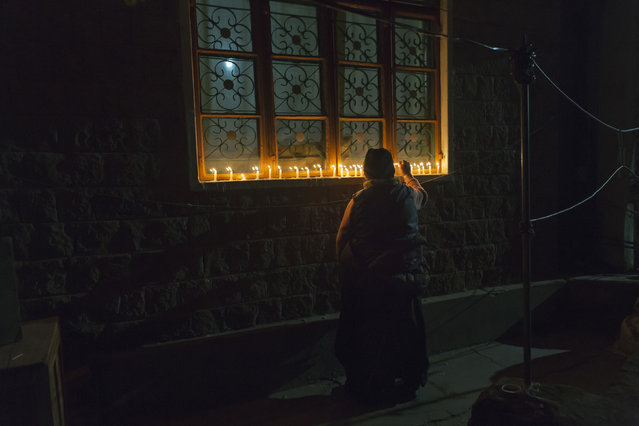 In this Sunday, December 2, 2018, file photo, an exile Tibetan lights candles in front of her house as Tibetans mark the death anniversary of Tsongkhapa, in Dharmsala, India. Tsongkhapa is the founder of the Gelug school of Tibetan Buddhism to which the Dalai Lama belongs. (Photo by Ashwini Bhatia/AP Photo)
