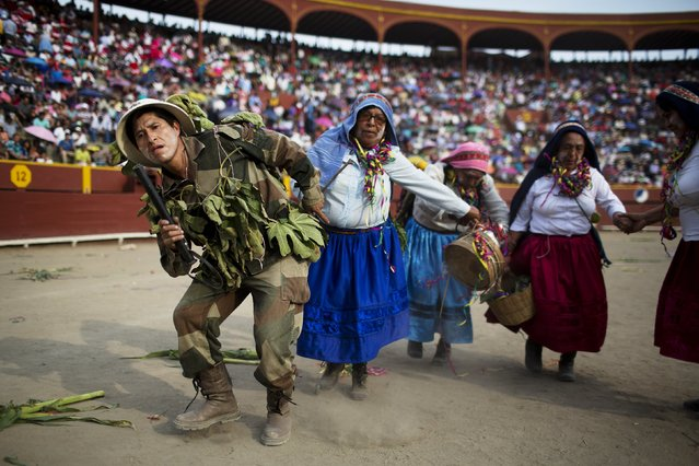 In this Sunday, March 29, 2015 photo, troupers, one dressed as a soldier, and the others as villagers, perform in the Vencedores de Ayacucho dance festival, in the Acho bullring in Lima, Peru. For the people of the Ayacuho region, the one-day dance competition contains macabre reminders of the bitter conflict for residents who fled the violence. The crowd fell silent when the dancers dressed like soldiers and rebels entered the ring and played out the killing of peasants with wooden and cardboard rifles. (Photo by Rodrigo Abd/AP Photo)