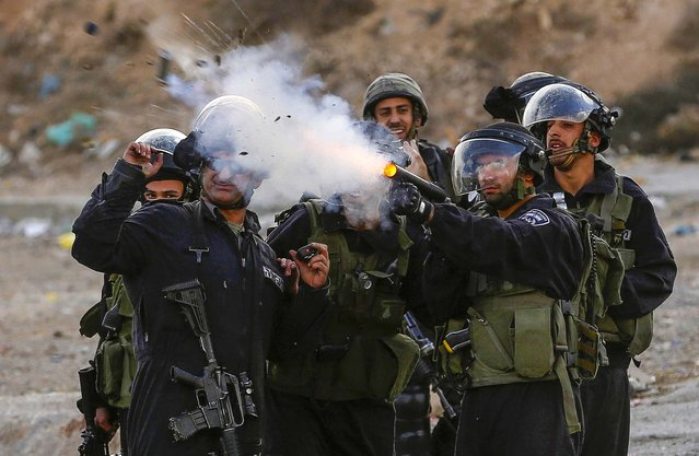 Israeli border police  fire a tear gas at stone-throwing Palestinian protesters during clashes following the funeral of Mahmoud Wajih Awad, at Qalandiya checkpoint near the West Bank city of Ramallah, on November 29, 2013. Palestinians said that Awad died on Thursday night in a Jerusalem hospital after succumbing to wounds he sustained during clashes with Israeli soldiers earlier this year. (Photo by Mohamad Torokman/Reuters)