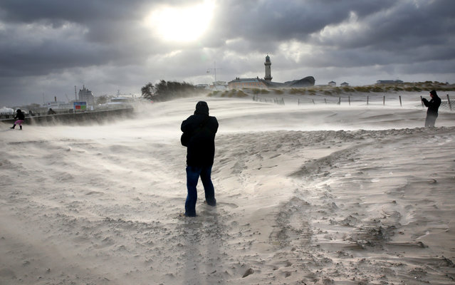 People stand on a dune while storm front Xaver blows heavily at the shore of  Rostock-Warnemuende, northern Germany, on December 6, 2013. Icy winter storms with hurricane-force force winds lashed northern Europe. (Photo by Bernd Wüstneck/AFP Photo/DPA)