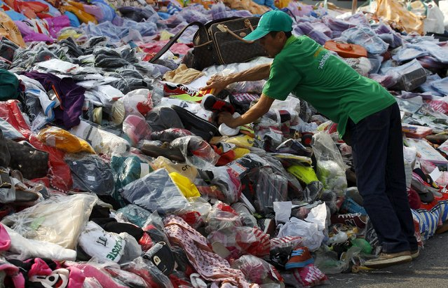 A Thai official arrange counterfeit goods before destroying them at Khlongluang Transportation Station in Pathumtani province, on the outskirts of Bangkok April 9, 2015. (Photo by Chaiwat Subprasom/Reuters)