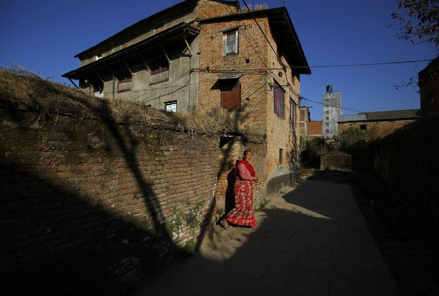 A woman walks out from a house at Sankhu in Kathmandu January 28, 2015. (Photo by Navesh Chitrakar/Reuters)