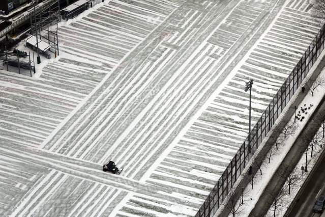 A lone plow clears a playground in lower Manhattan, photographed from New York's One World Trade Center building, Monday, January 9, 2017. As the East Coast waits to thaw out from a weekend icy mess, another storm is bringing rain and the potential of the worst flooding in more than a decade to the West coast. (Photo by Richard Drew/AP Photo)