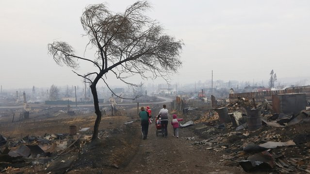 Family members walk away while passing the debris of destroyed buildings in the settlement of Shyra, damaged by recent wildfires, in Khakassia region, April 13, 2015. (Photo by Ilya Naymushin/Reuters)