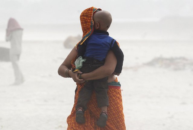 A woman protects her child during a dust storm on the banks of river Ganga in the northern Indian city of Allahabad, April 4, 2015. (Photo by Jitendra Prakash/Reuters)