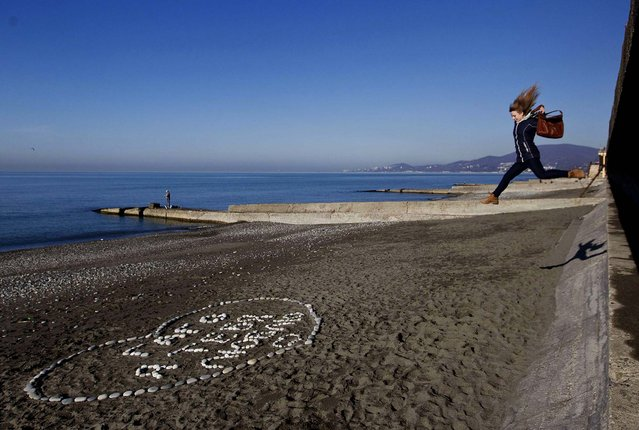 A woman jumps onto the beach in the Adler district of the Black Sea resort city of Sochi, Russia, on December 24, 2013. Sochi will host the 2014 Winter Olympics in February. (Photo by Maxim Shemetov/Reuters)
