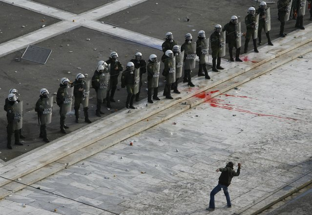 A protester throws a stone at police in front of the Greek Parliament building during clashes in Athens, in this December 12, 2008 file photo. (Photo by John Kolesidis/Reuters)