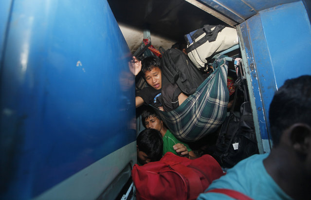 A man from India's northeastern state sits in a hammock tied inside an overcrowded train bound for the Assam state at the railway station in Kolkata, August 18, 2012. (Photo by Rupak De Chowdhuri/Reuters)