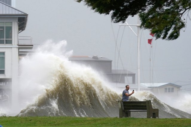 A man takes pictures of high waves along the shore of Lake Pontchartrain as Hurricane Ida nears, Sunday, August 29, 2021, in New Orleans. (Photo by Gerald Herbert/AP Photo)