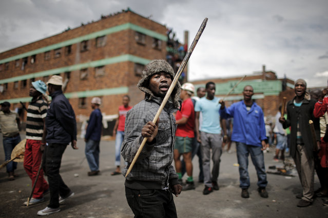 Zulu protesters demonstrate against foreign migrants outside their hostel in the Jeppestown district of Johannesburg on April 17, 2015. (Photo by Marco Longari/AFP Photo)