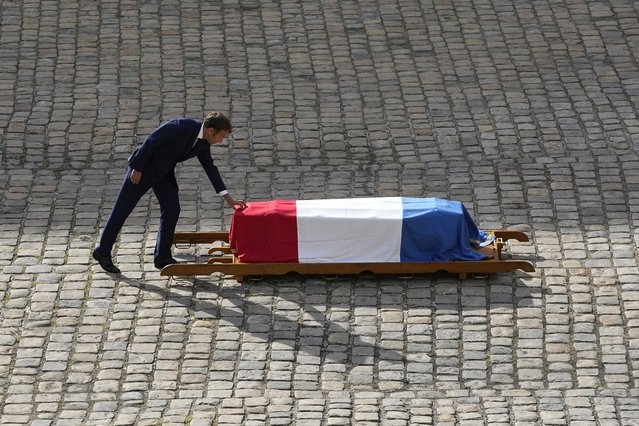 French President Emmanuel Macron touches the coffin of Jean-Paul Belmondo during a tribute ceremony for the late French actor at the Hotel des Invalides, Thursday, September 9 2021 in Paris. (Photo by Michel Euler/AP Photo)