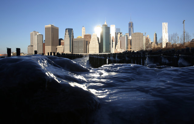 Ice forms on rocks on the Brooklyn waterfront across from lower Manhattan in New York, Tuesday, January 7, 2014. The high temperature is expected to be 10 degrees in the city but wind chills will make it feel more like minus 10. (Photo by Peter Morgan/AP Photo)
