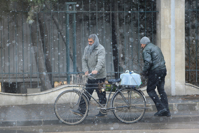 A man walks with his bicycle during a snow storm in Damascus, Syria January 28, 2017. (Photo by Ali Hashisho/Reuters)