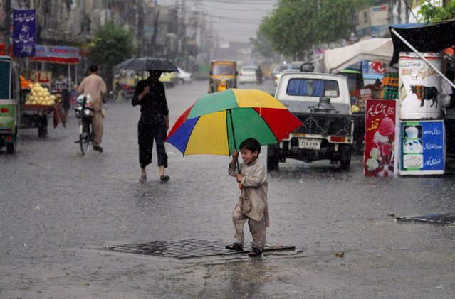 A boy holds an umbrella as he crosses a road in heavy rain, in Rawalpindi, Pakistan, Monday, April 27, 2015. Officials in northwestern Pakistan say heavy rain has killed at least 30 people. (Photo by Anjum Naveed/AP Photo)
