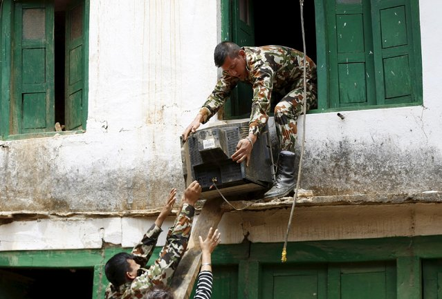 Nepalese soldiers help people salvage belongings from their houses damaged by Saturday's earthquake in Sangachowk, Nepal, April 29, 2015. (Photo by Olivia Harris/Reuters)