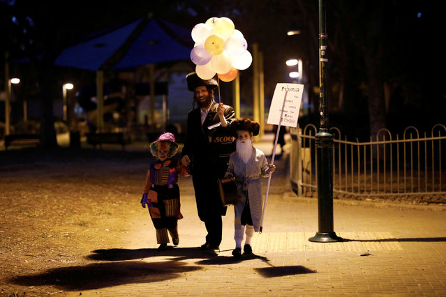 An Ultra Orthodox Jewish family dressed in costumes walk during the Jewish holiday of Purim, Israel, March 20, 2019. (Photo by Amir Cohen/Reuters)